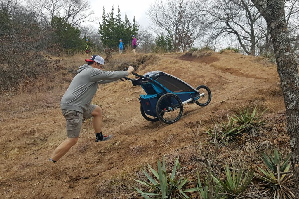 Man pushing Thule Cross up a dirt hill in trailer mode.