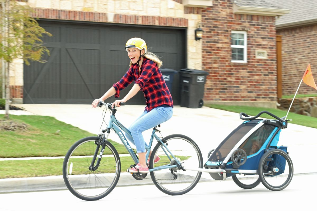 Mom riding bike while pulling the Thule Cross bike trailer behind her