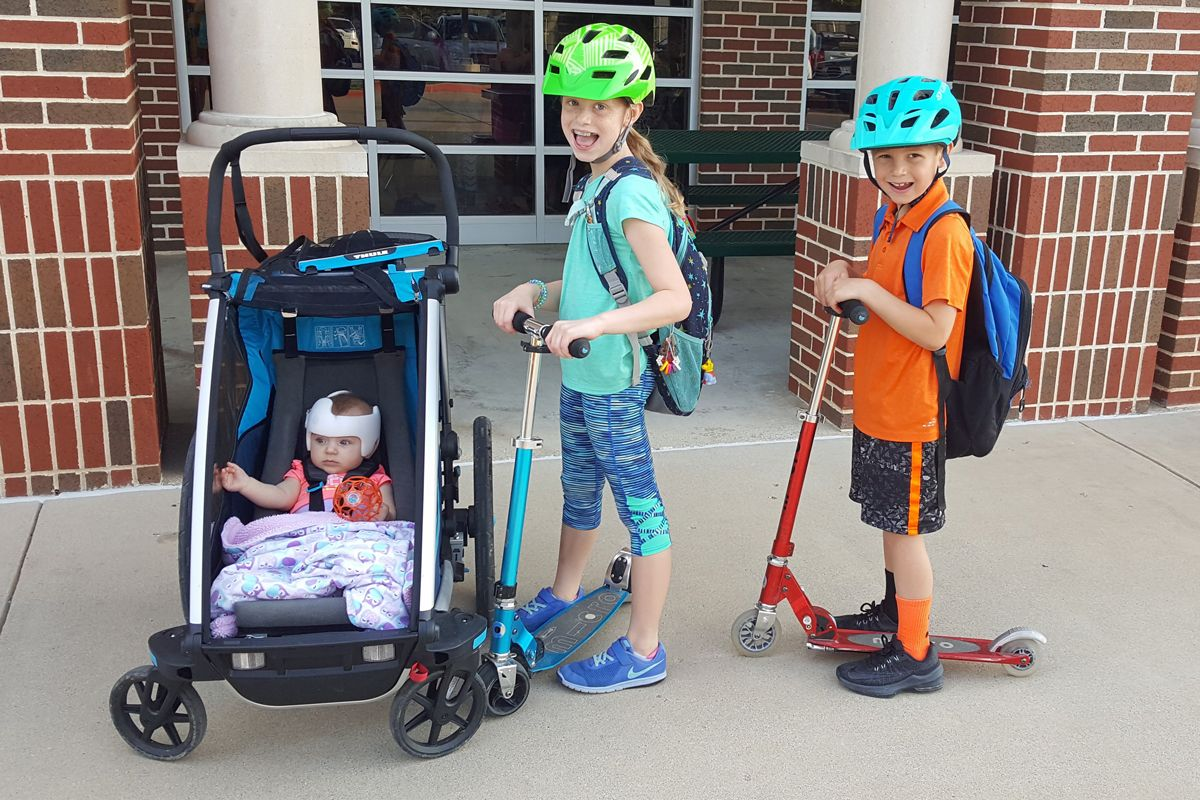 Baby sitting in Thule Infant Sling in the Thule Cross in stroller mode, next to brother and sister on Micro scooters.