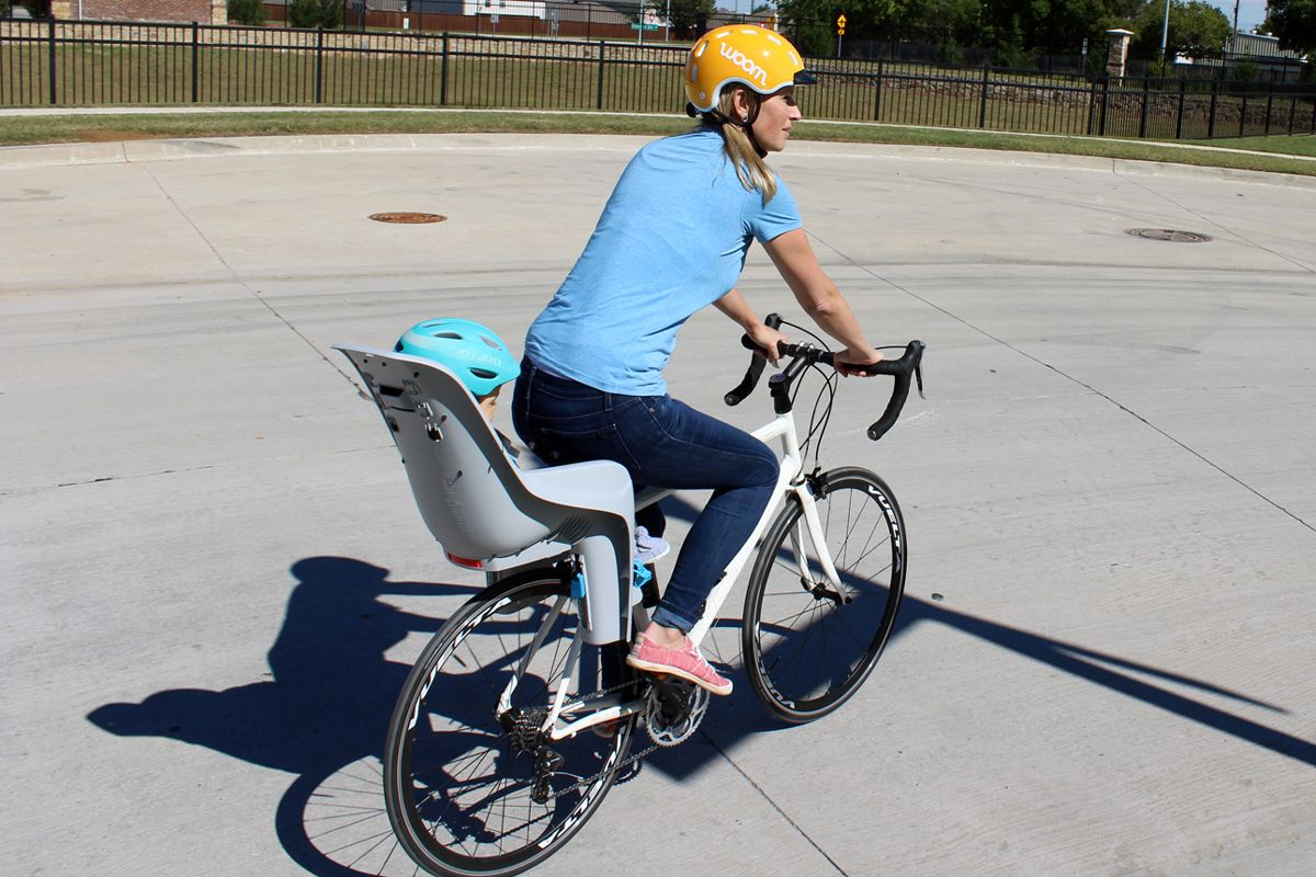 Mom riding with her baby in the Thule RideAlong Lite child bike seat.