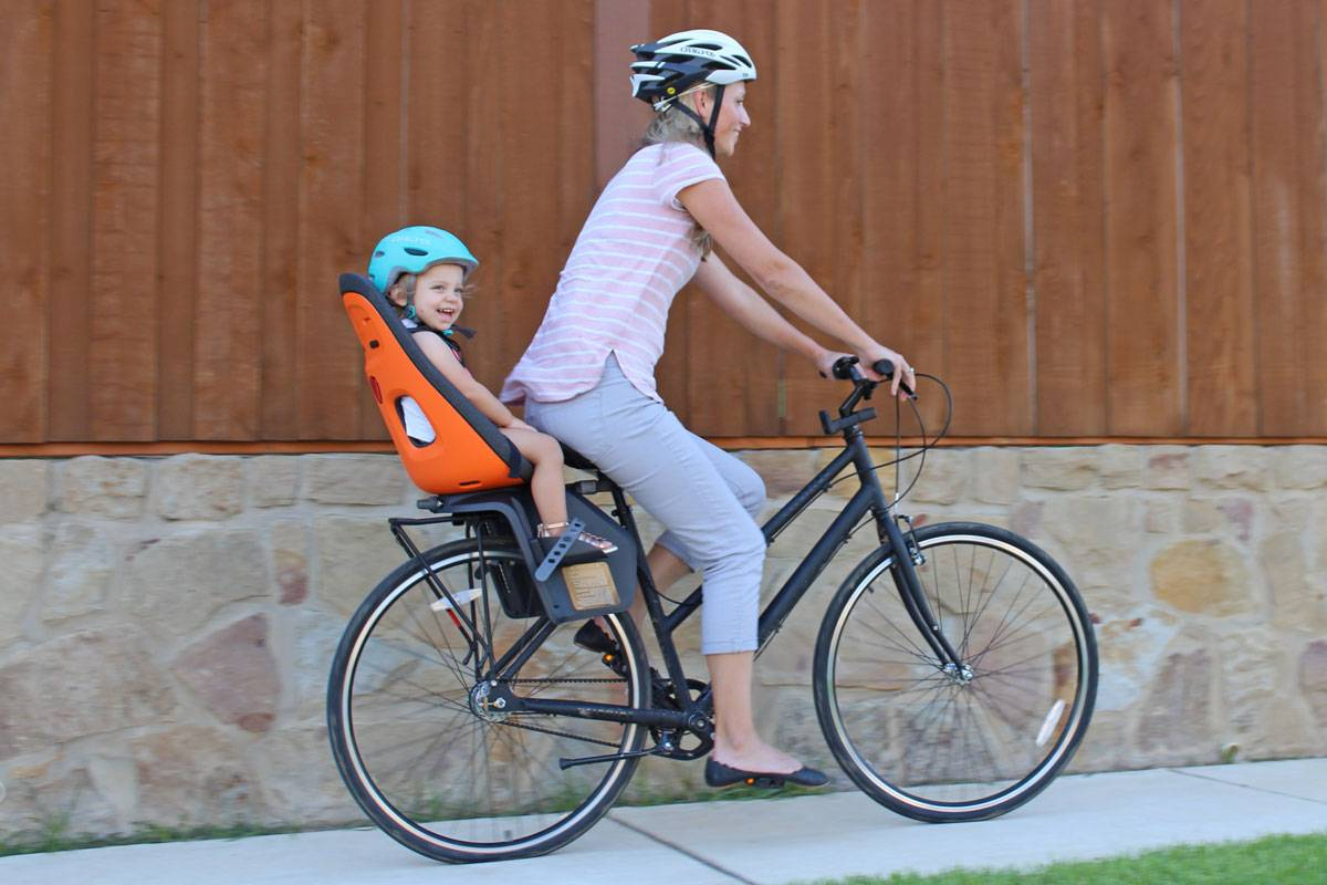 Mom riding with toddler in Thule Yepp Next Maxi child bike seat down the sidewalk