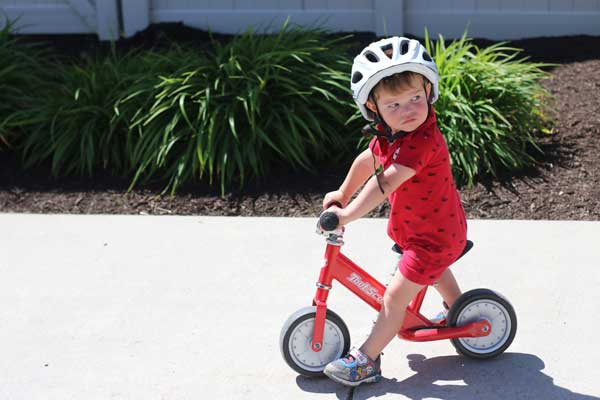 Toddler riding Toot Scoot balance bike in red
