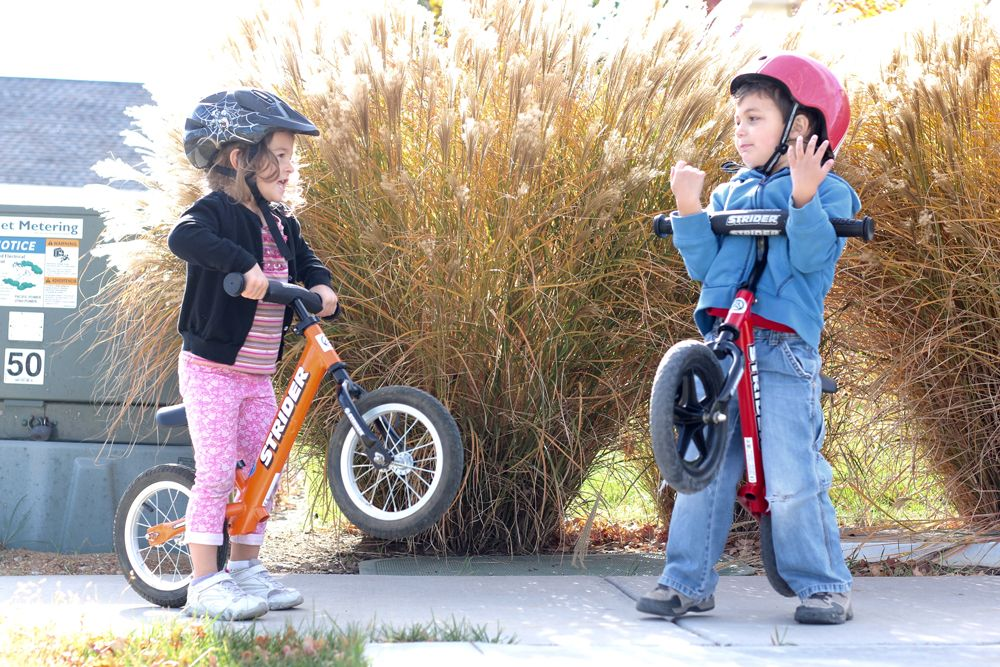 two preschoolers lifting up their Strider balance bikes while talking to each other.
