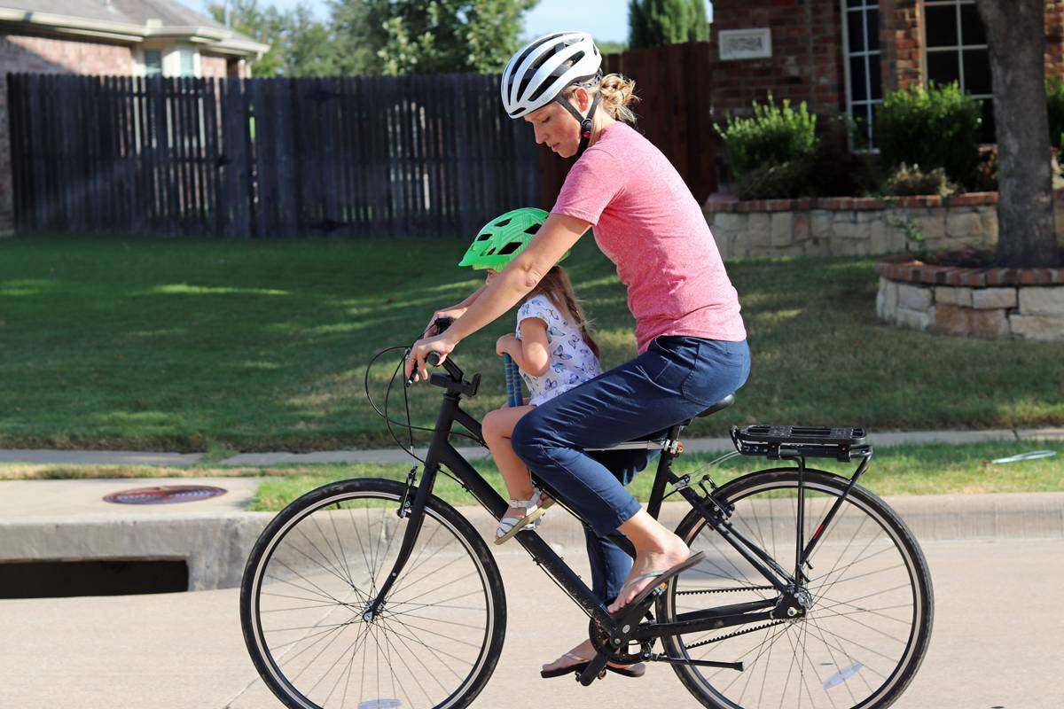 Mom on bike with 3 year old girl, who is sitting on the UrRider Child Bike Seat