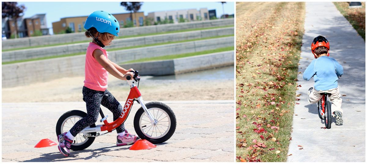 Two toddlers riding red woom 1 balance bikes on the sidewalk