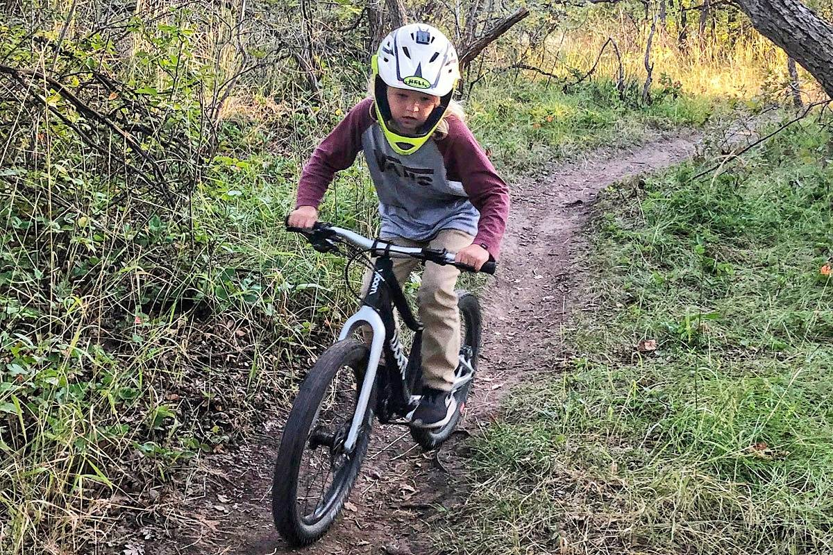 "woom OFF 20"" on single track. 7 year old riding with full face helmet."