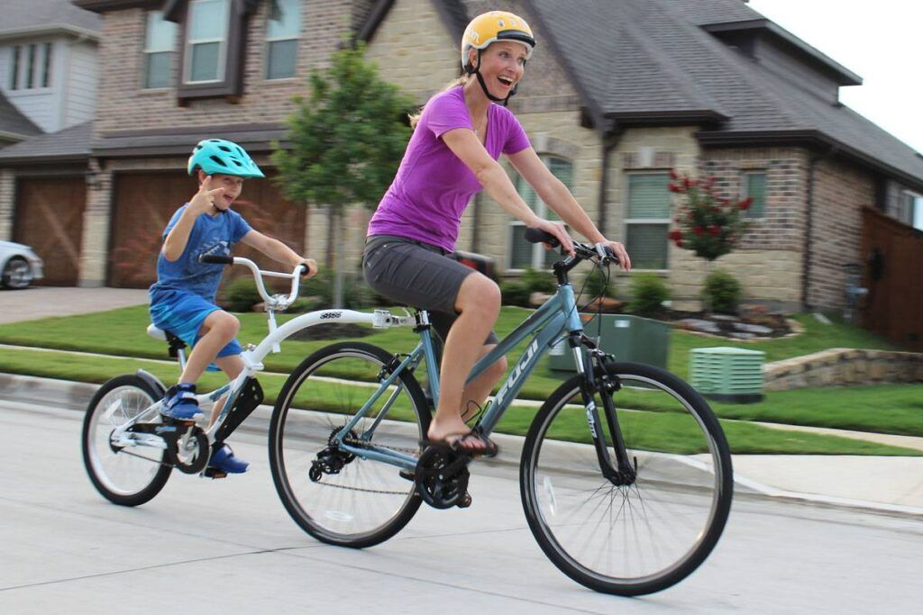 Mom riding bike with her son behind her on the Weeride Co-Pilot tag along bike