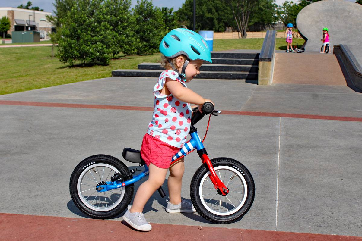 young girl riding her balance bike at a skate park