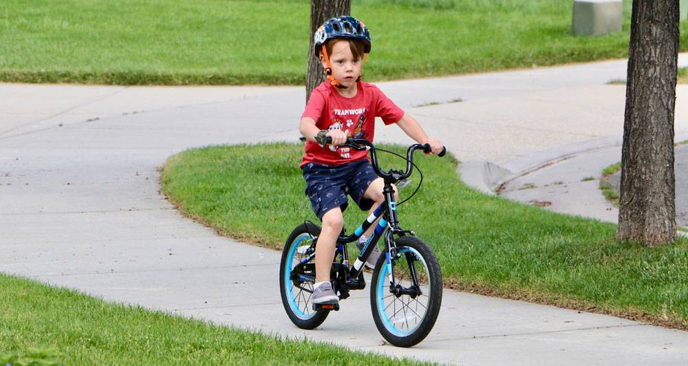 "4 year old boy riding the Guardian 16"" Ethos bike down the sidewalk"