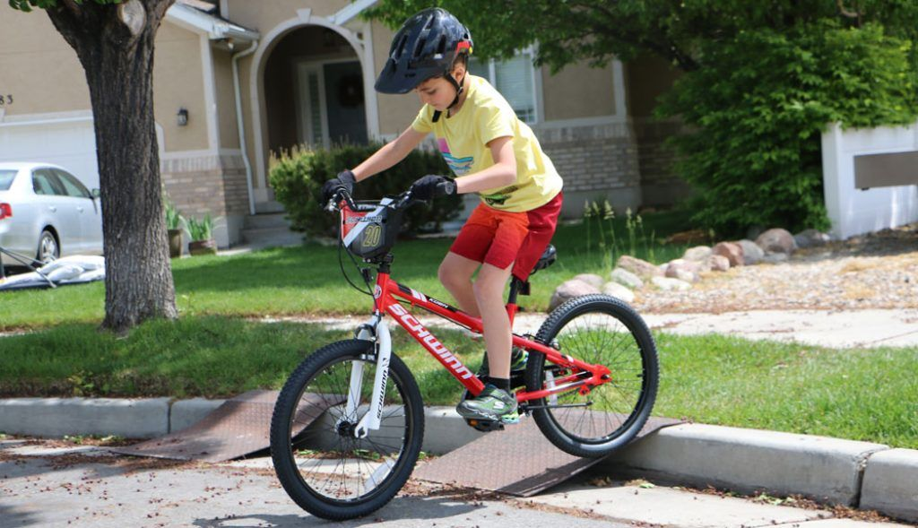 boy riding on a red schwinn koen 20 inch smartstart bike