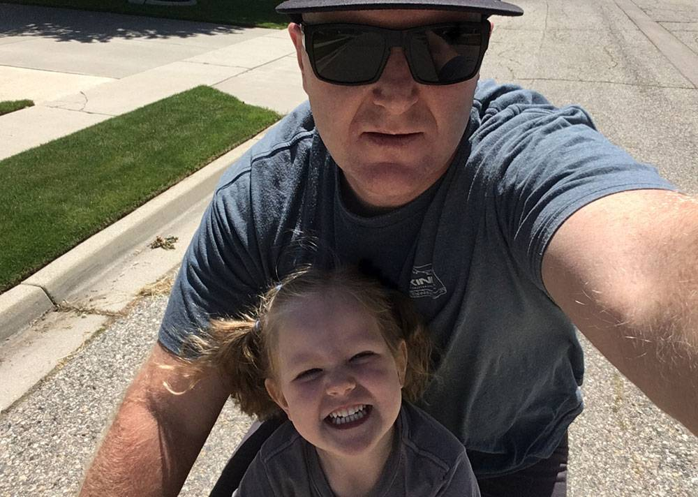 Dad and 4 year old daughter taking a selfie on the Kids Ride Shotgun child bike seat