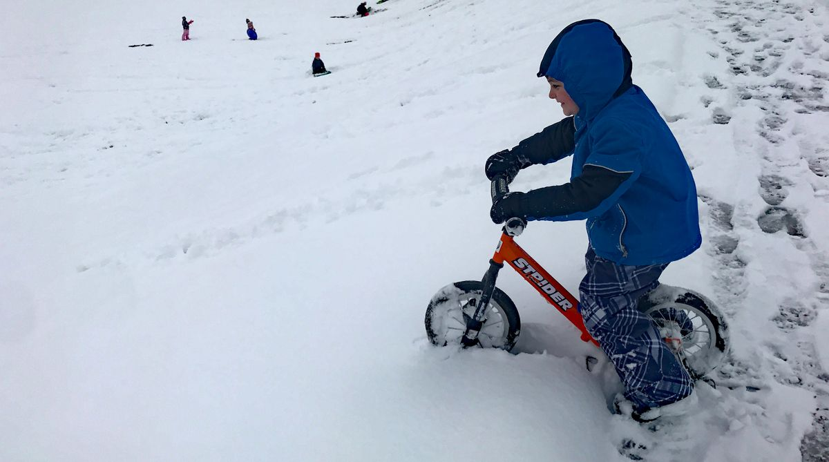 4 year old riding the Strider balance bike with ski set down a snowy hill