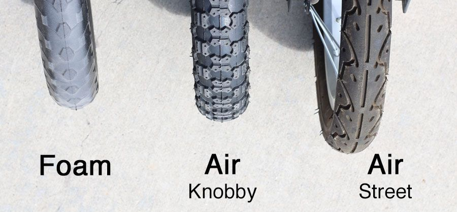 Three balance bike tires lined up next to each other - foam, knobby air, and street tread air.