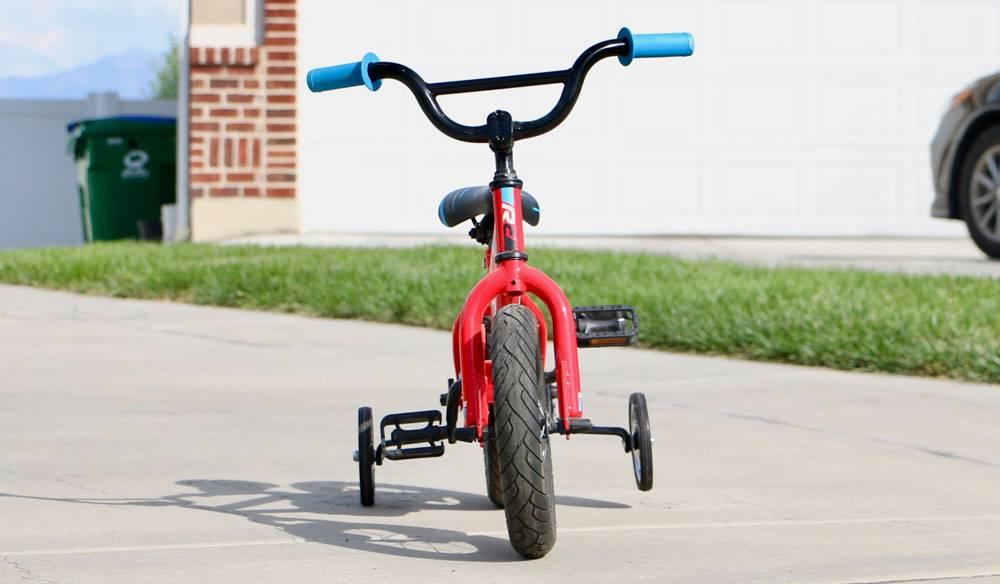 "12"" kid's bike with training wheel, tilted to one side as it leans on one training wheel."