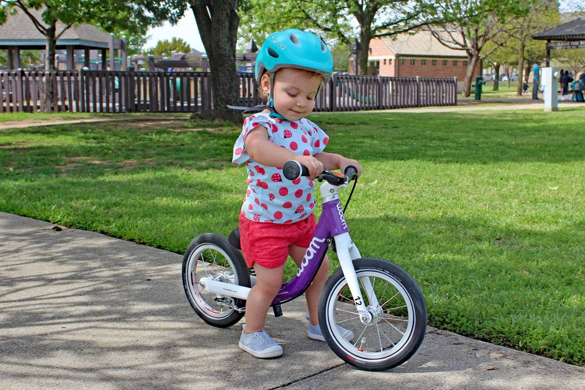 Young child riding a woom bikes balance bike in park