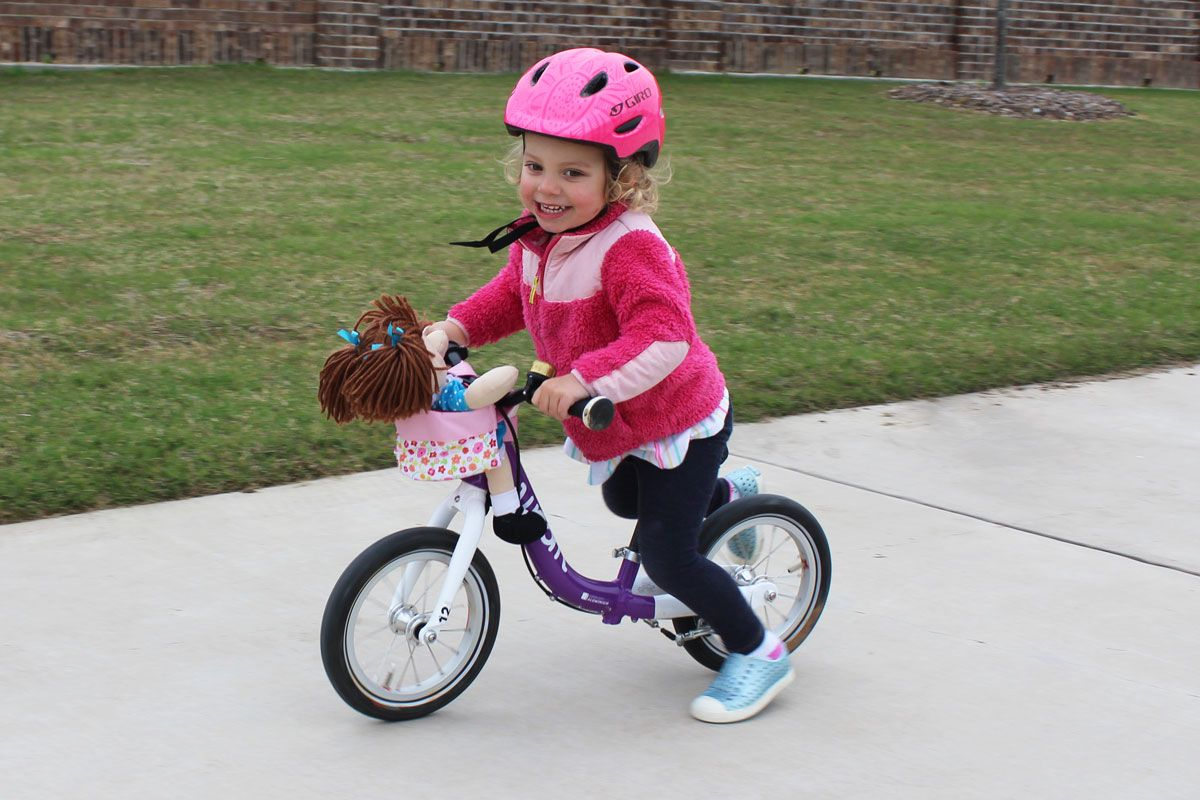 2 year old riding woom 1 balance bike with her dolly in the Haba doll bike seat