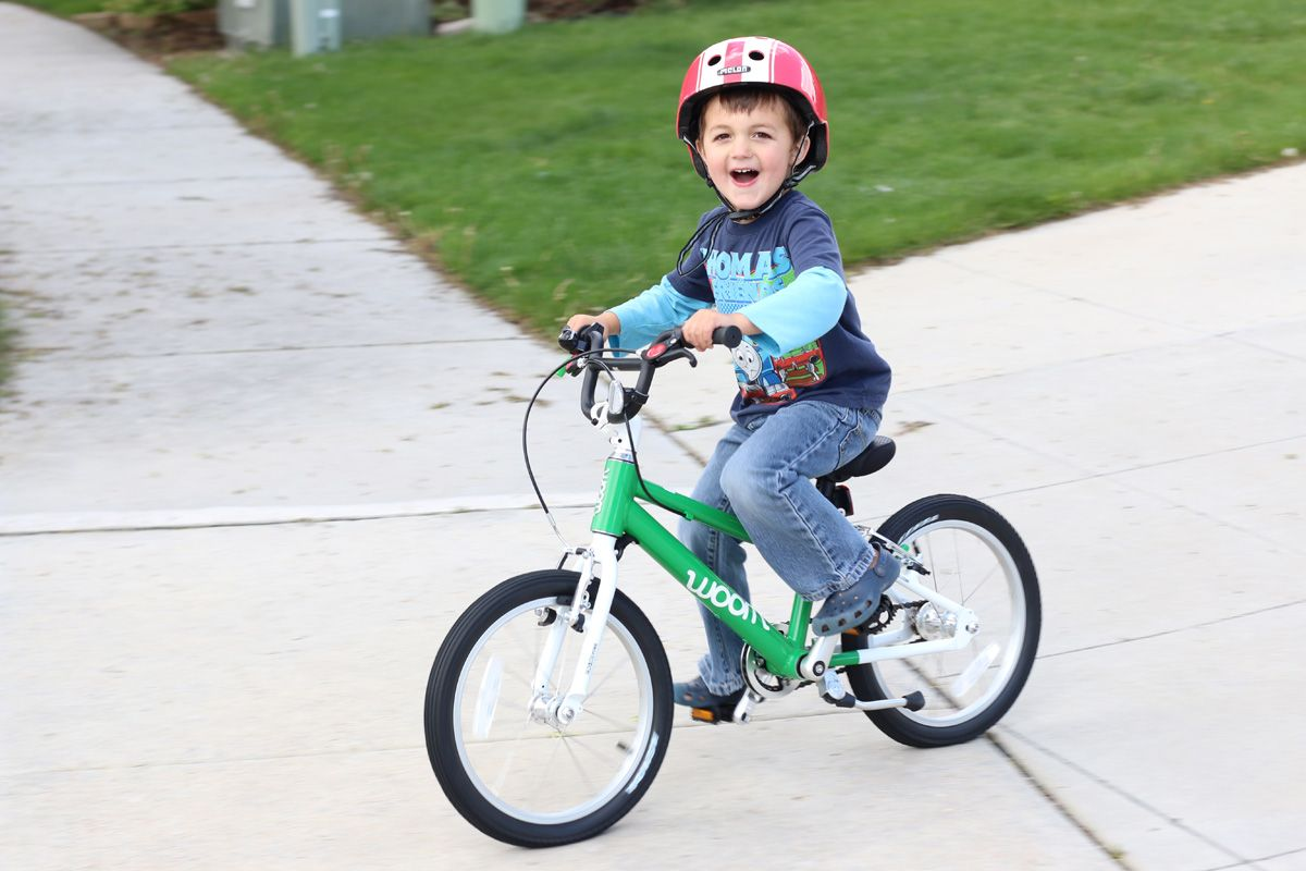 young child riding a green woom bikes 16 bikes
