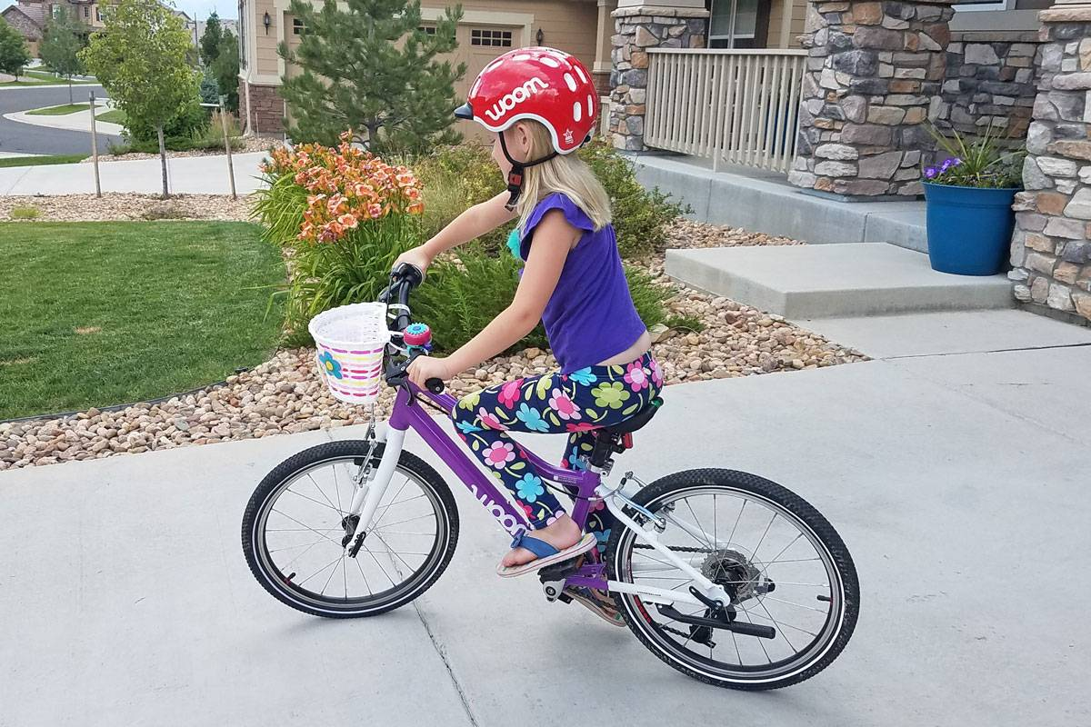 Young child riding a blue woom bikes in her driveway