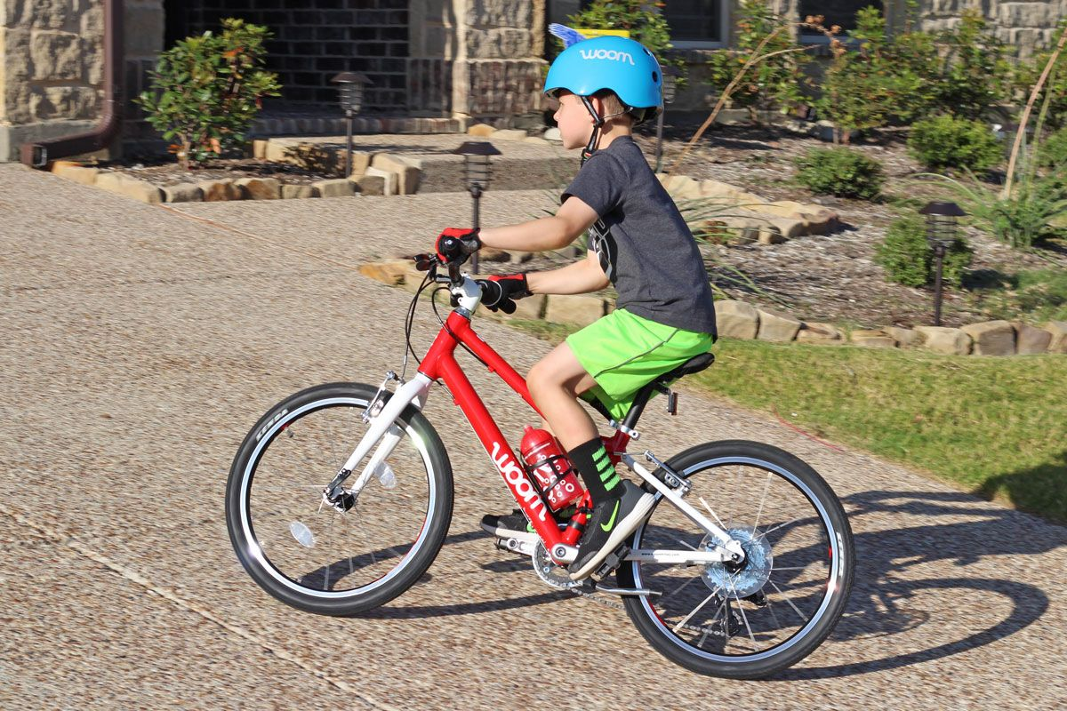 a boy riding a red woom bikes on the driveway