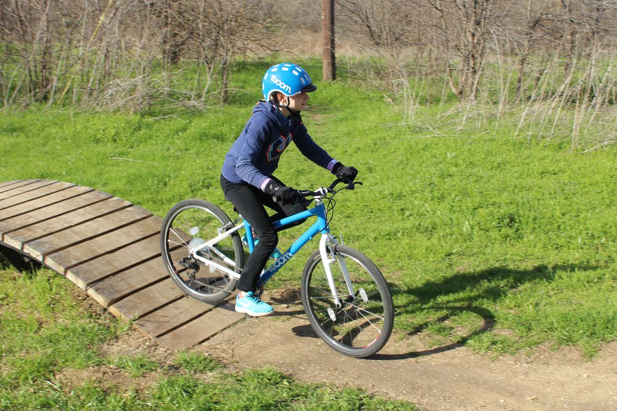 child riding a blue woom bikes at a bike park