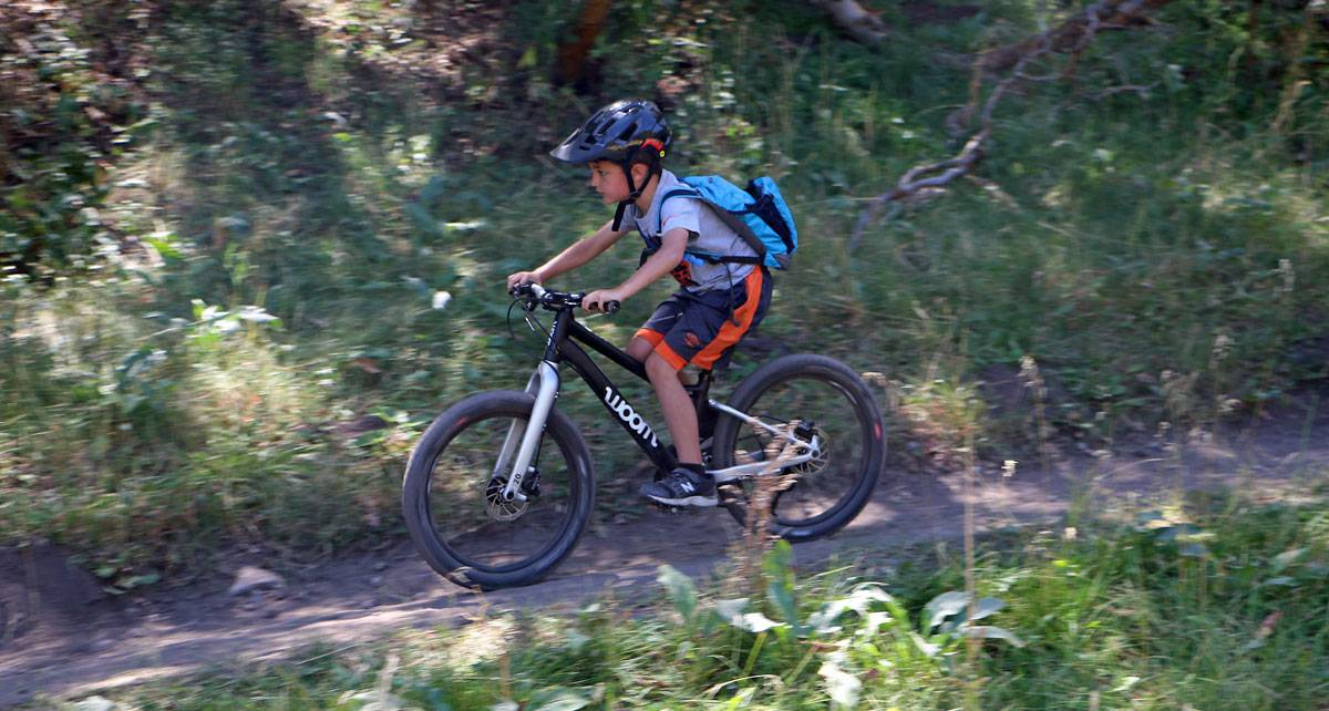 7 year old riding a trail on the woom OFF mountain bike