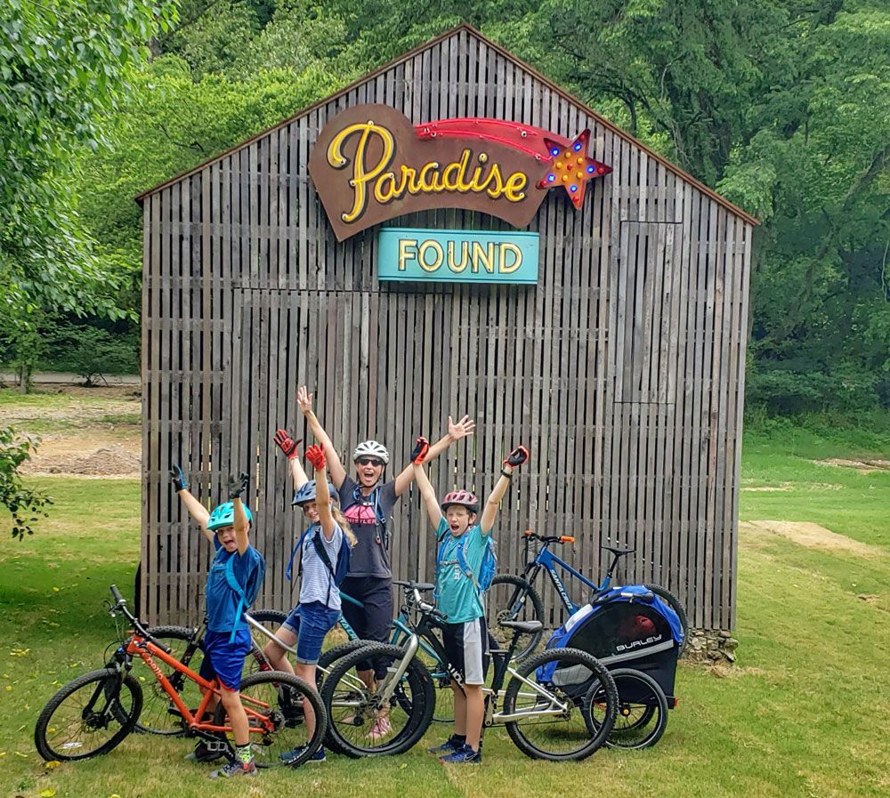 Family standing with bikes in front of Paradise Found barn at Coler Mountain Bike Preserve
