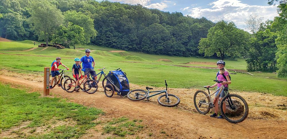 Family standing with bikes with North Skills Park at Slaughter Pen in Bentonville