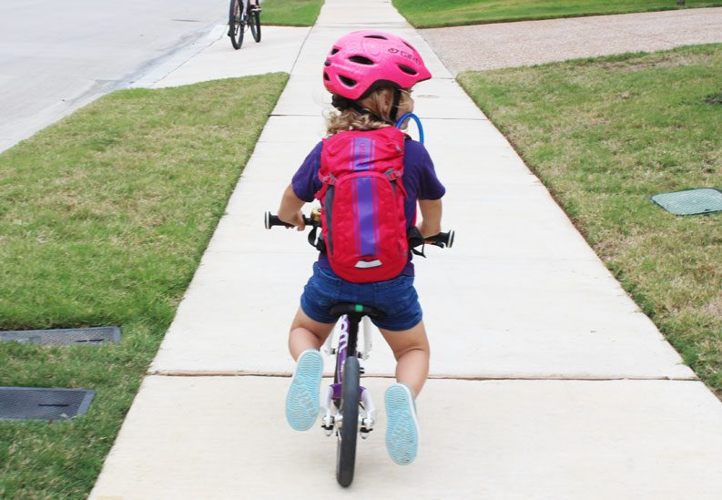 image of young toddler riding a balance bike from behind while wearing a camelbak mini mule hydration pack