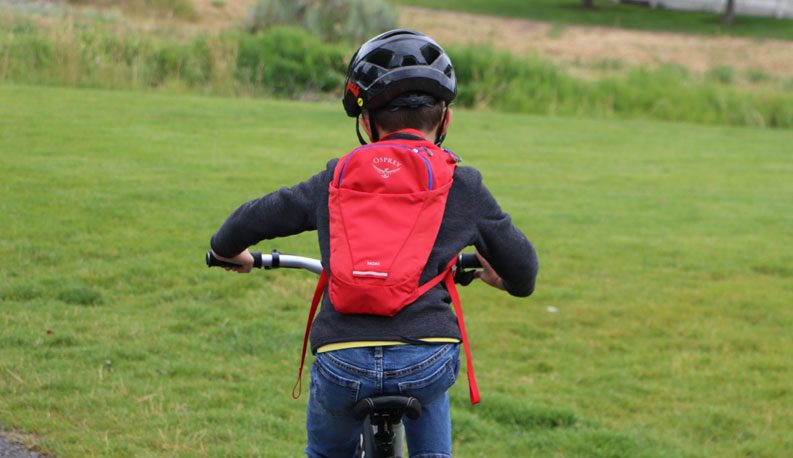 young boy riding a bike while wearing a red Osprey Moki kids hydration pack