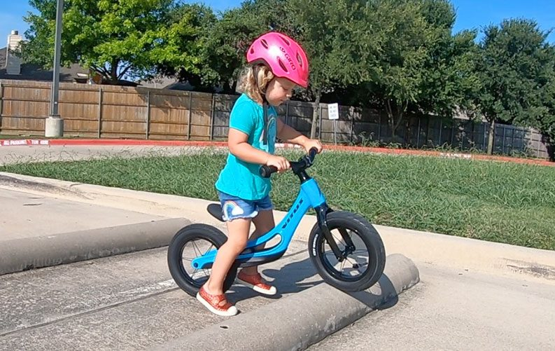 Toddler riding Vitus Smoothy balance bike over parking curb