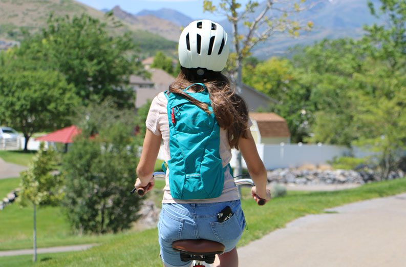 13 year old girl riding her bike while wearing a teal Osprey kitsuma 3 hydration pack