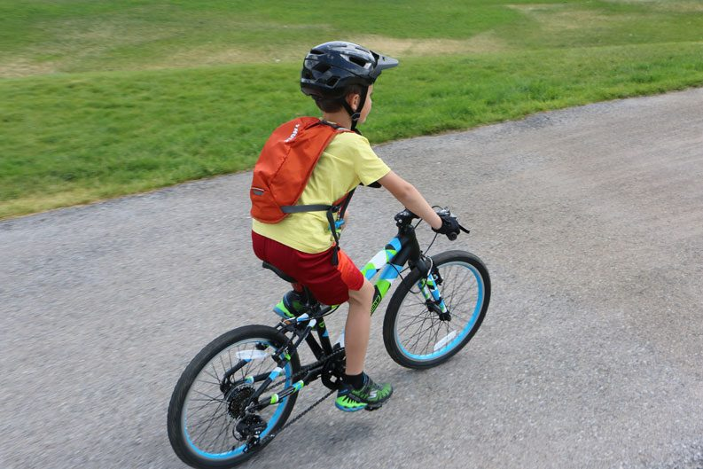 Young boy riding his Guardian bike while wearing an orange Thule Uptake Youth hydration pack
