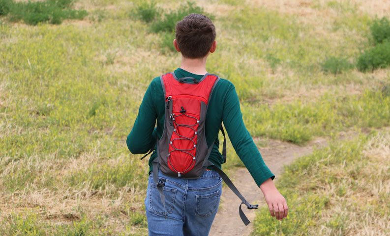 boy hiking while wearing a red unigear hydration pack. shown from the rear