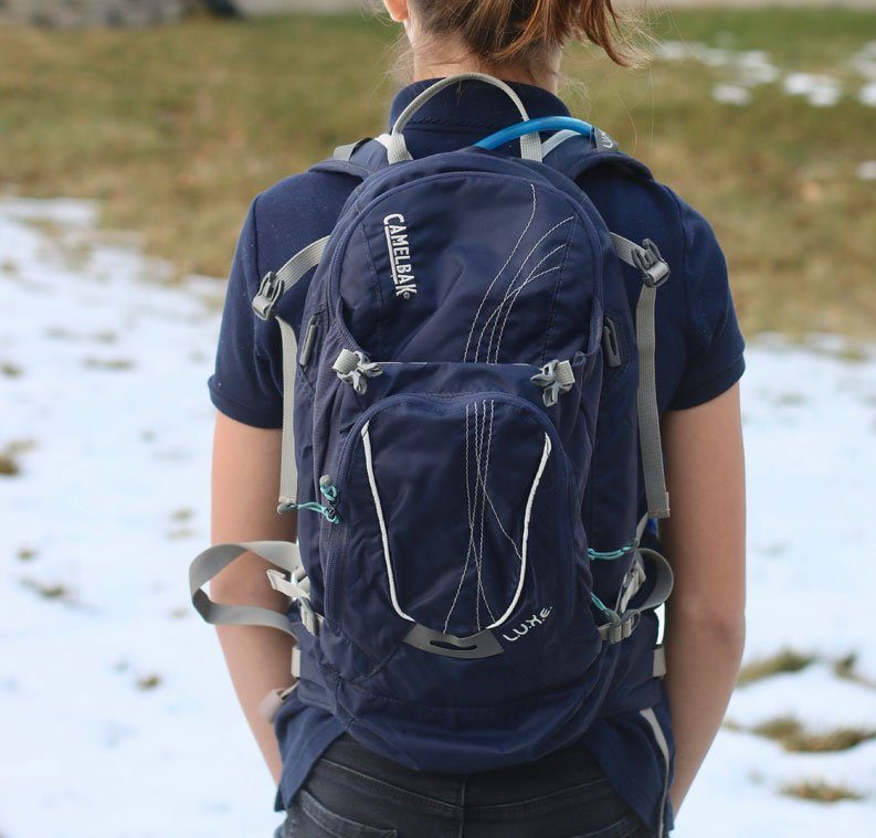 13 year-old wearing a blue camelbak luxe hydration pack. Shown from the rear