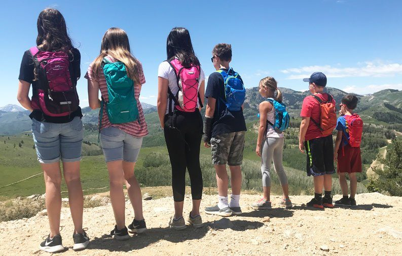 Group of 7 children on a mountain wearing hydration packs