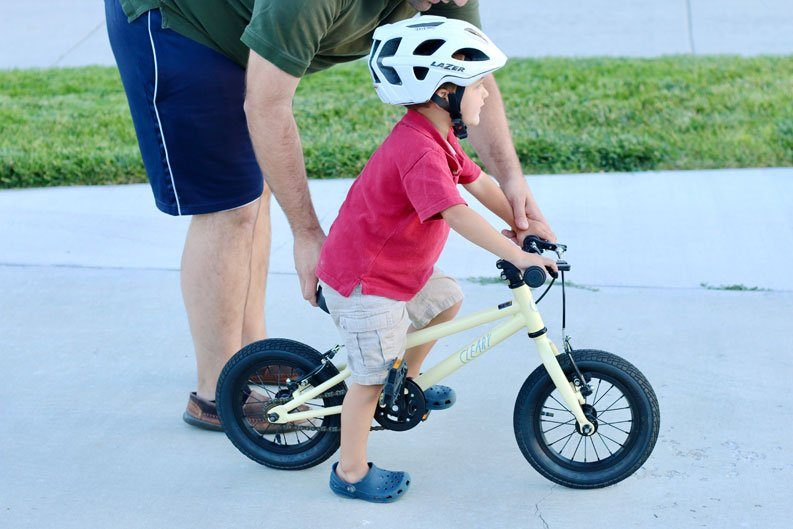 young child learning how to pedal a bike while riding a cleary gecko 12 inch bike