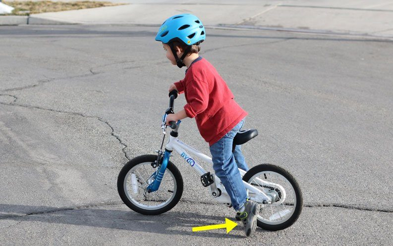 young child learning to pedal by bike by starting with a push