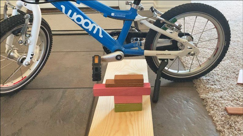 DIY bike trainer for teaching a child to learn to pedal. Made out of kids blocks.