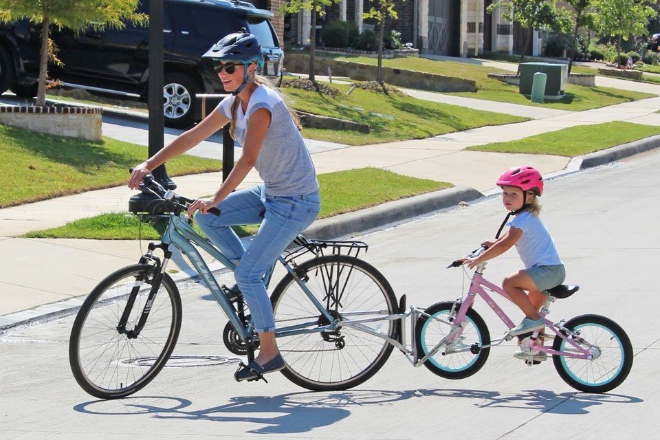 Mom riding with 2.5 year old on her bike using the FollowMe Tandem bike coupling device