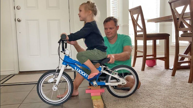 3 year old sitting on her bike with dad helping her learn to pedal