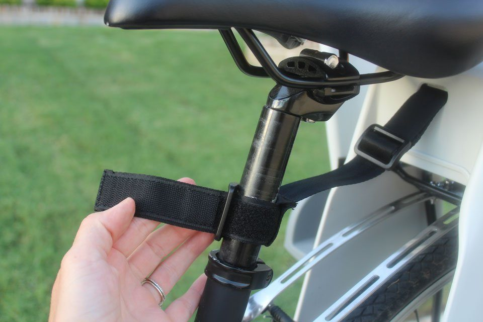 Back up safety strap of Topeak BabySeat II being attached to adult bike seat post
