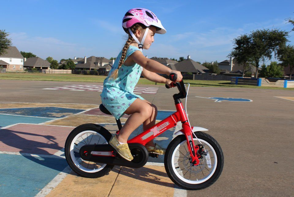 4 year old riding SmarTrike Xtend convertible balance bike in pedal bike mode