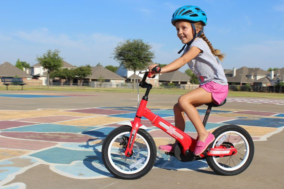 5 year old riding SmarTrike Xtend convertible balance bike in pedal bike mode