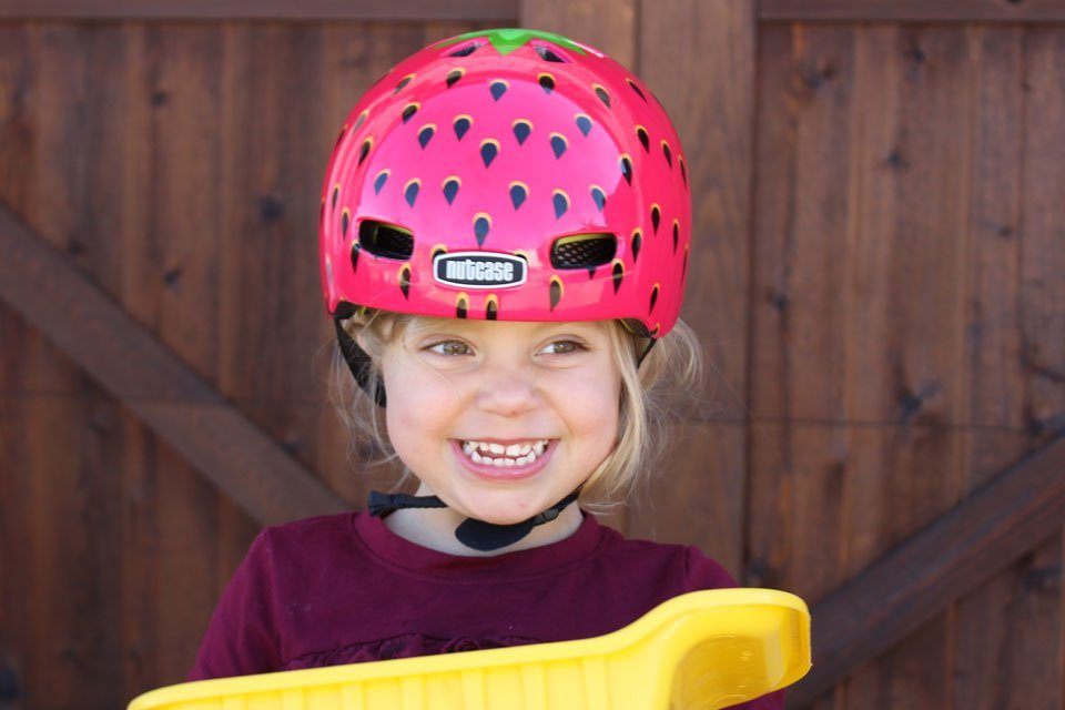 Toddler smiling and wearing the Nutcase Baby Nutty bike helmet