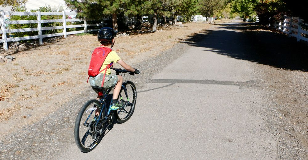 8 year old riding Vitus Kids 24 inch bike down a gravel trail