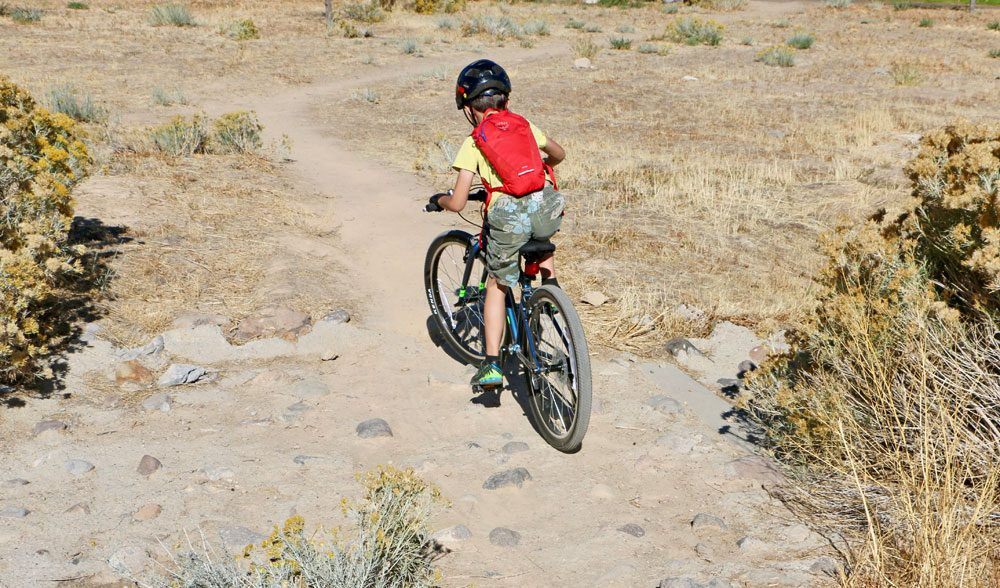 8 year old riding Vitus Kids 24 inch bike over rocky terrain