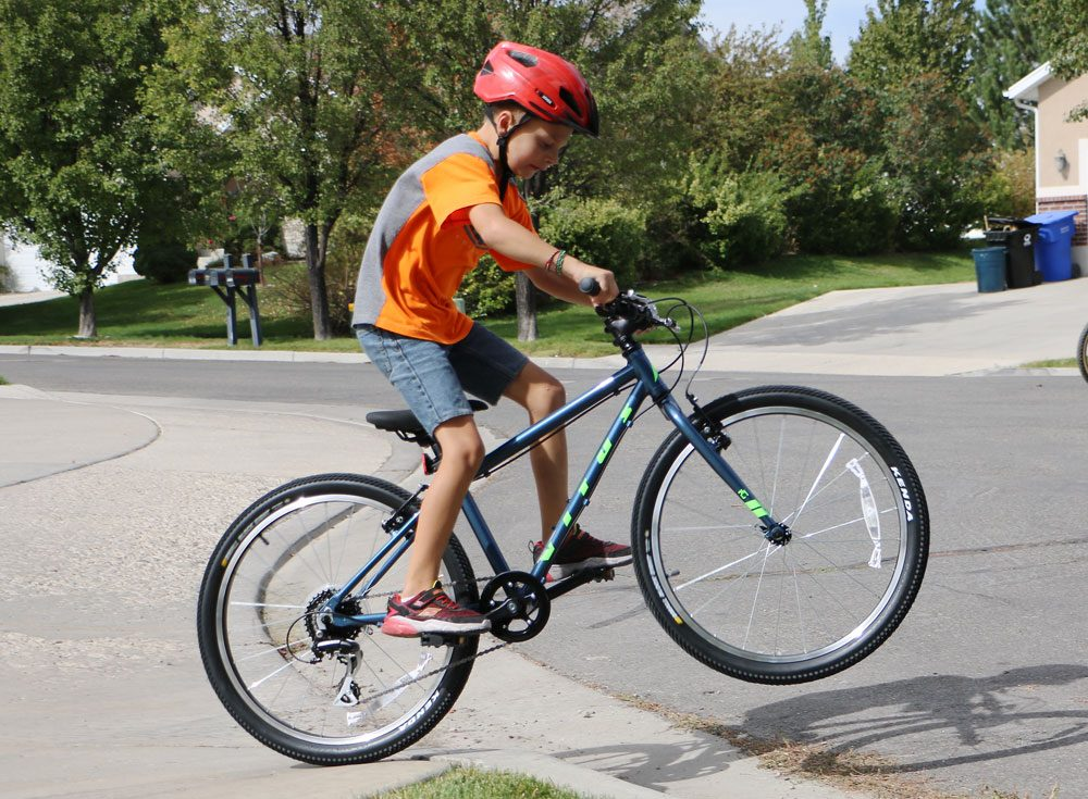 9 year old riding Vitus Kids 24 inch bike off the curb