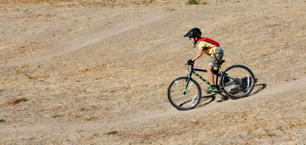 8 year old riding Vitus Kids 24 inch bike down a dirt trail