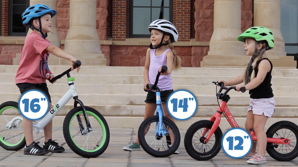 "Three kids, each on a balance bike. On has 16"" wheels, one has 14"" wheels, and one has 12"" wheels"